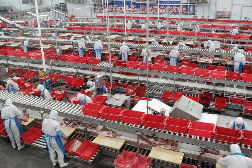 Workers sort cuts of fresh pork in a processing plant of pork producer WH Group in Zhengzhou, Henan province China, on Nov 24, 2017.