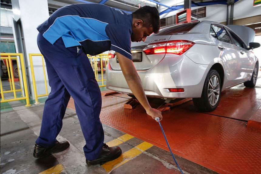 A staffer inserting an emission probe into the exhaust pipe of a car that is undergoing high-idling test at a workshop along Sin Ming Drive on April 9, 2018.