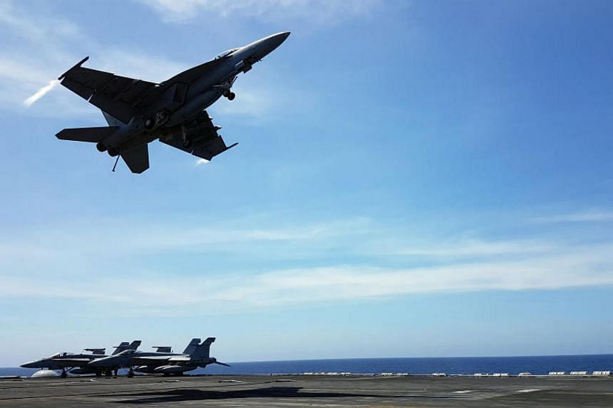 An F18 fighter takes off from the deck of the USS Theodore Roosevelt while transiting the South China Sea on April 10, 2018.