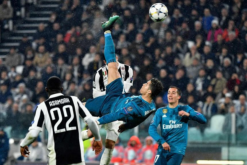Portuguese forward Cristiano Ronaldo (in blue) scores during the UEFA Champions League quarter-final first leg football match between Juventus and Real Madrid at the Allianz Stadium in Turin on April 3, 2018.