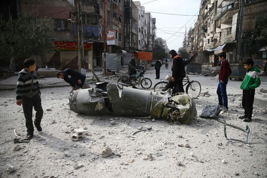 People inspect missile remains in the besieged town of Douma in Damascus, Syria, on Feb 23, 2018.