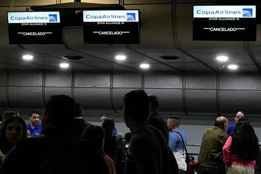 """Screens that read """"cancelled"""" hang above Copa Airlines counters at the Simon Bolivar airport in Caracas, Venezuela, on April 6, 2018."""
