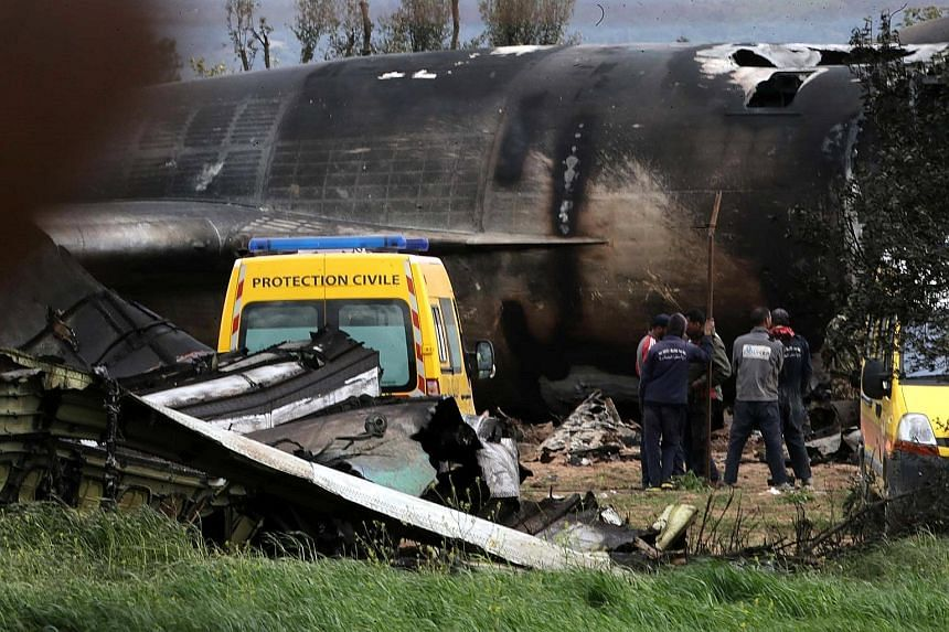 Rescuers at the wreckage of the crashed plane. The Ilyushin IL-76 transport plane was bound for Tindouf in south-west Algeria.