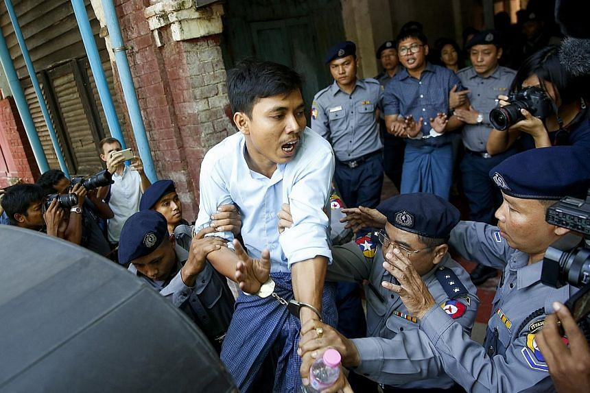 Reuters journalists Kyaw Soe Oo (in front) and Wa Lone being led away after their hearing in Yangon yesterday - when a judge rejected a request for the dismissal of a case against them. They are accused of possessing secret government papers.