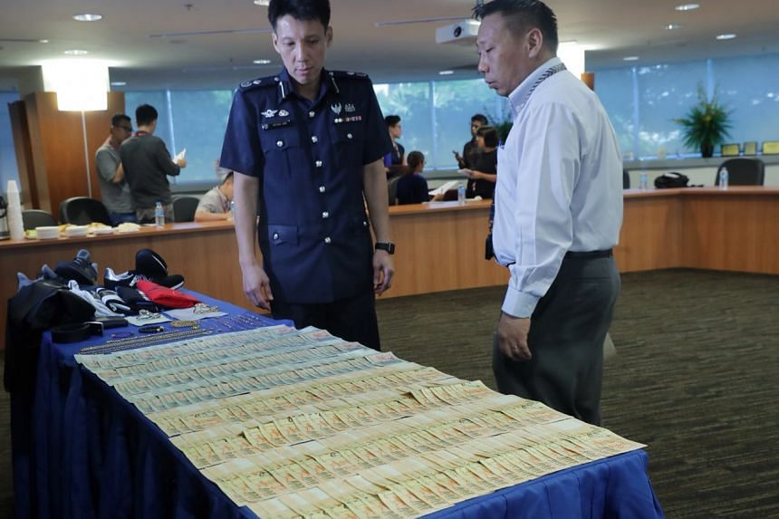 Commander of Central Police Division, Assistant Commissioner Arthur Law (left), 48, with Inspector Ang Wee Kiat, 38. Mr Law said it is not common for people to perform bitcoin transactions in person, and with such large amounts of cash.