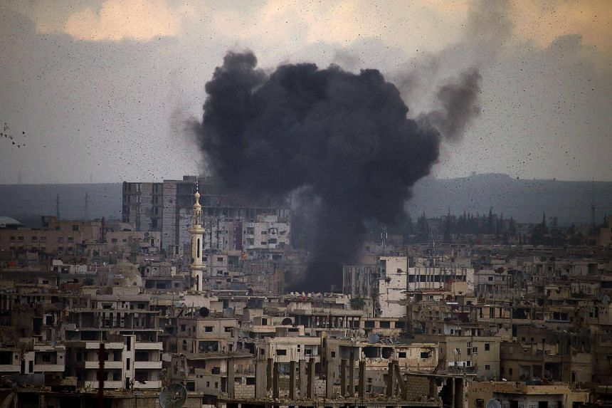 Smoke rises from buildings following a reported regime surface-to-surface missile strike on a rebel-held area on the southern Syrian city of Daraa on March 23, 2018.