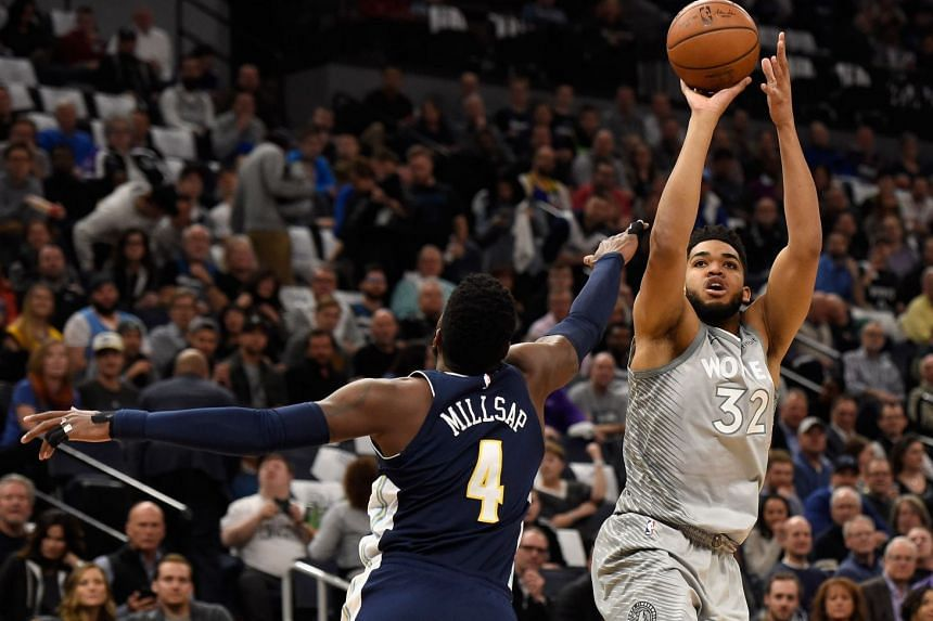 Minnesota Timberwolves centre Karl-Anthony Towns (right) shooting the ball over Denver Nuggets forward Paul Millsap during their NBA game on April 11, 2018.