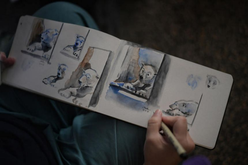 Polytechnic lecturer Anita Ryanto, 47, with her drawings of the zoo's iconic polar bear, Inuka.