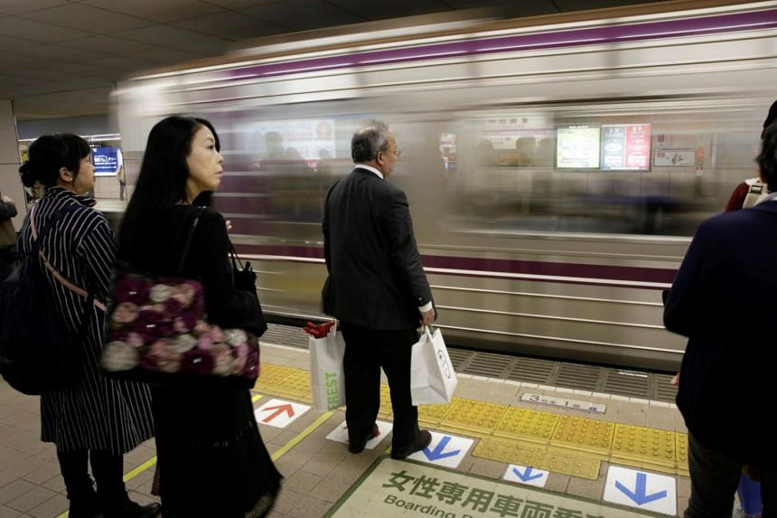File photo showing commuters waiting for a train in Osaka, western Japan, on Oct 24, 2017.