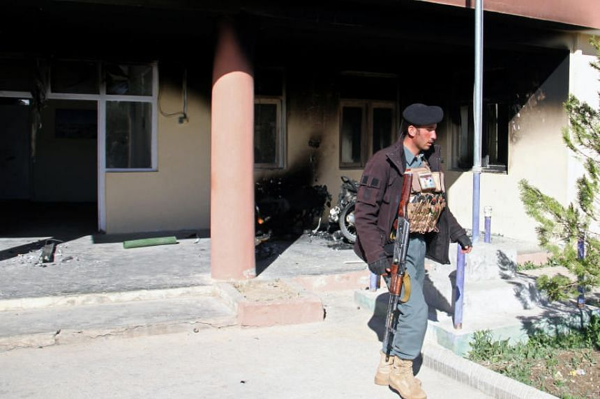 An Afghan policeman walks at the government district building after a Taleban attack in Khawaja Omari district of Ghazni province, Afghanistan, on April 12, 2018.