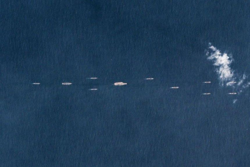 China's sole operational aircraft carrier, the Liaoning (centre), sailing with other ships at sea, south of China's southern Hainan island on March 26, 2018.