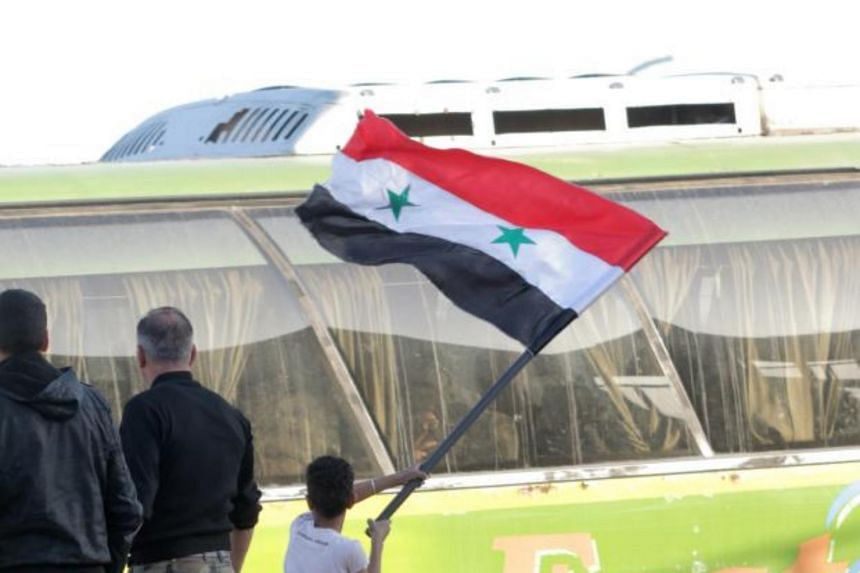A boy waves a Syrian flag as government buses evacuated al-Islam Army's fighters from Douma, in eastern Ghouta, Syria, on April 9, 2018.