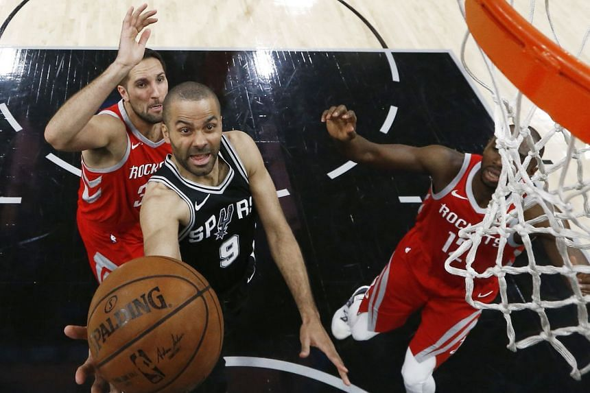 Tony Parker (centre) goes to the basket against Houston Rockets player Ryan Anderson (left).