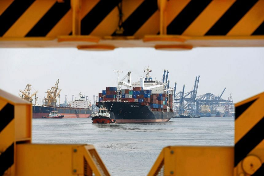 A cargo ship being towed in by tugboats in Tanjung Priok Port, Jakarta, in 2016.