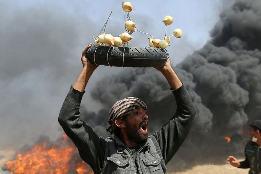 A Palestinian demonstrator shouts as he carries a tyre with onions during clashes with Israeli troops, April 6, 2018.
