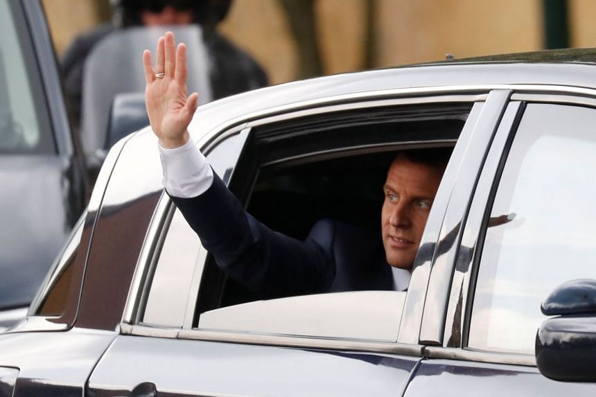 Macron waves from his car as he leaves a TV interview in Berd'huis, France, April 12, 2018.