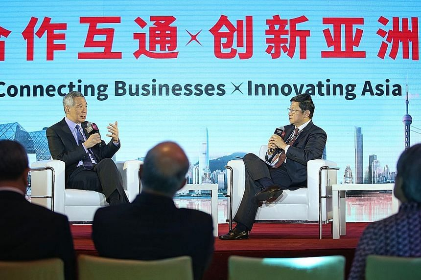 Prime Minister Lee Hsien Loong speaking at DBS Asian Insights Conference's Leadership Dialogue in Shanghai yesterday, moderated by Mr Robin Hu, head of Temasek's sustainability and stewardship group.