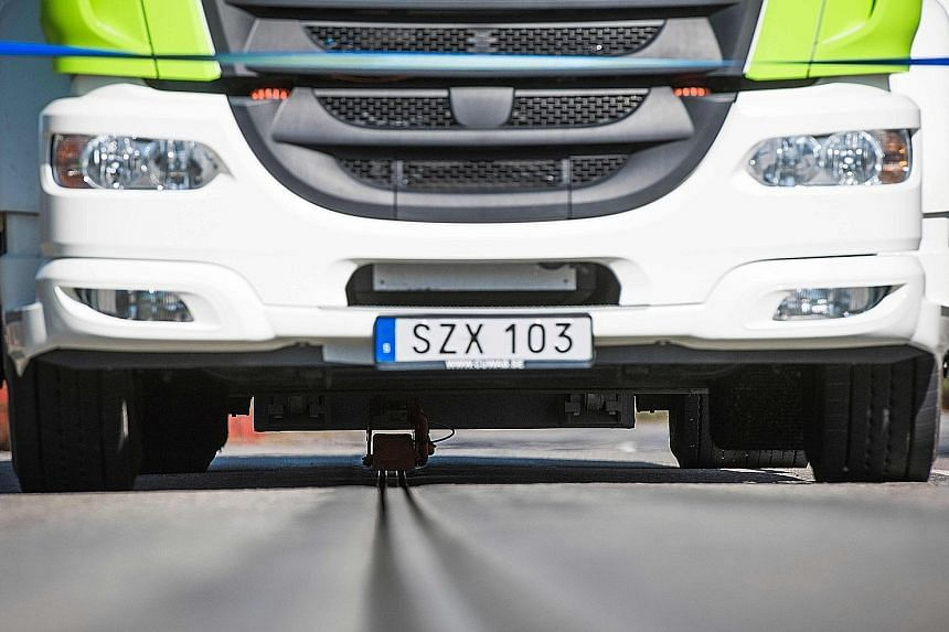 An electric truck on the world's first electrified road at Sweden's Stockholm Arlanda airport on Wednesday. Energy is transferred from two tracks of rail in the road through a movable arm attached to the bottom of the vehicle. When the vehicle stops,
