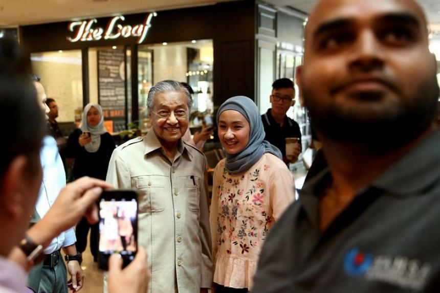 A shopper poses for a photo with former Malaysian prime minister Tun Dr Mahathir Mohamad at Dpulze Shopping Centre in Kuala Lumpur, Malaysia.