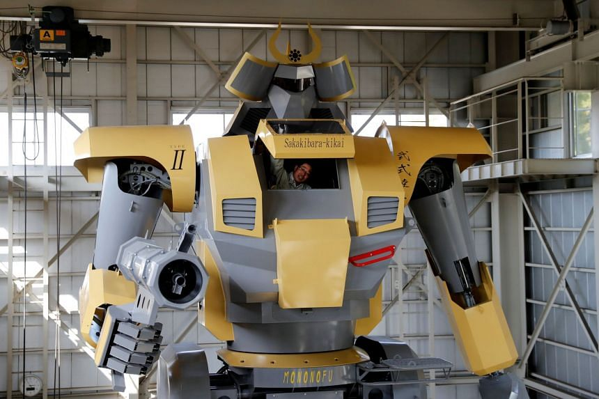 Sakakibara Kikai's engineer Masaaki Nagumo opens a hatch from the cockpit of the bipedal robot Mononofu during a demonstration at its factory in Shinto Village, Gunma Prefecture, Japan on April 12, 2018.