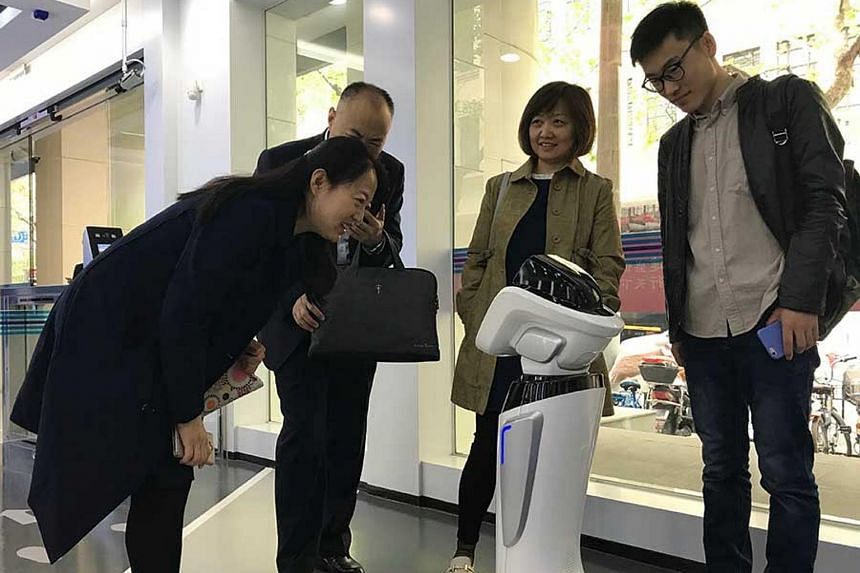 "Customers interact with a robot at an ""unmanned"" bank outlet in Shanghai on April 12, 2018."