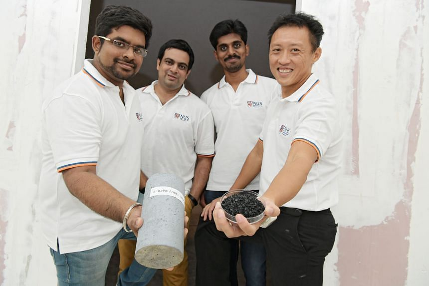 (From left) Research assistant Manikandan Jayaraj, PhD student Souradeep Gupta, research assistant Chakradha Pedapati and Dr Kua Harn Wei with biochar, a material produced when heat is used to decompose sawdust, and a concrete column containing bioch