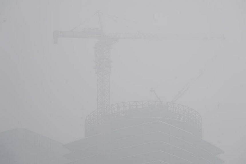 A building under construction is seen amid heavy smog in Beijing's central business area, on April 2, 2018.