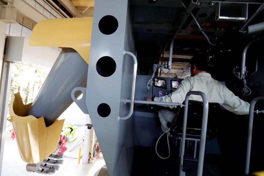 Sakakibara Kikai's engineer Masaaki Nagumo controls the bipedal robot Mononofu from its cockpit.