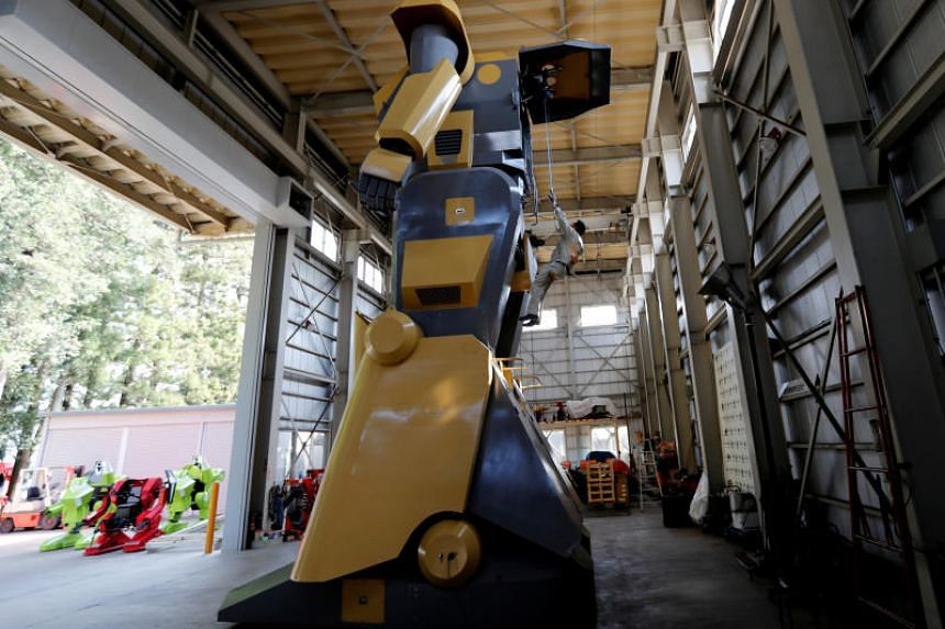 Sakakibara Kikai's engineer Masaaki Nagumo rides a lift to board the bipedal robot Mononofu.