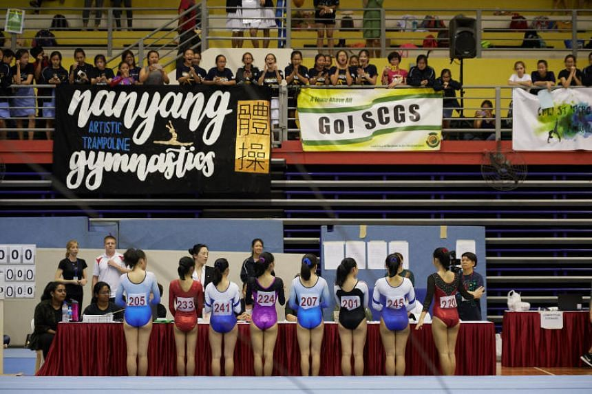 Supporters in the stands cheer on the final day of the Schools National B Division artistic gymnastic championships at Bishan Sports Hall on April 13, 2018.