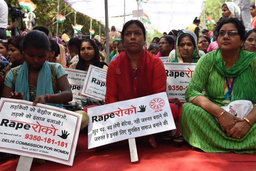 Women sit during a protest in New Delhi on April 13, 2018, against the brutal gang rape and murder of an eight-year-old girl.