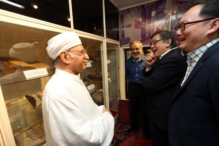 Syed Hassan Al-Attas, Imam and head of Ba'alwie mosque, shows historical Islamic scripts and books to Pastor Yang Tuck Yoong (second from right) and Pastor Lim Lip Yong  (right), after lunch at the Ba'alwie mosque on April 13, 2018.