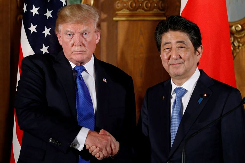 Trump and Abe shake hands at the end of a news conference in Tokyo, in November 2017.