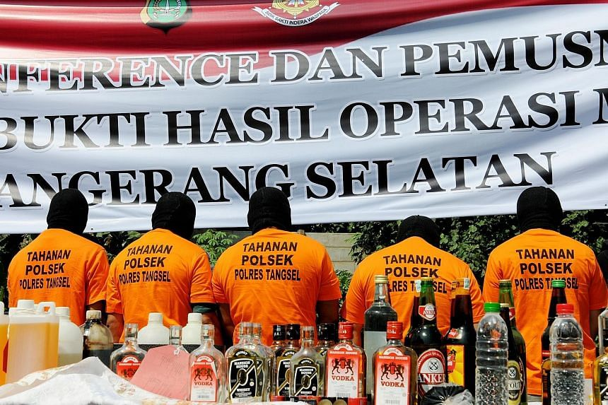 Suspects arrested for producing and selling illegal homemade alcohol were put on parade by Indonesian police during a public display in South Tangerang, on the outskirts of the Indonesian capital Jakarta, yesterday. Thousands of booze bottles were de