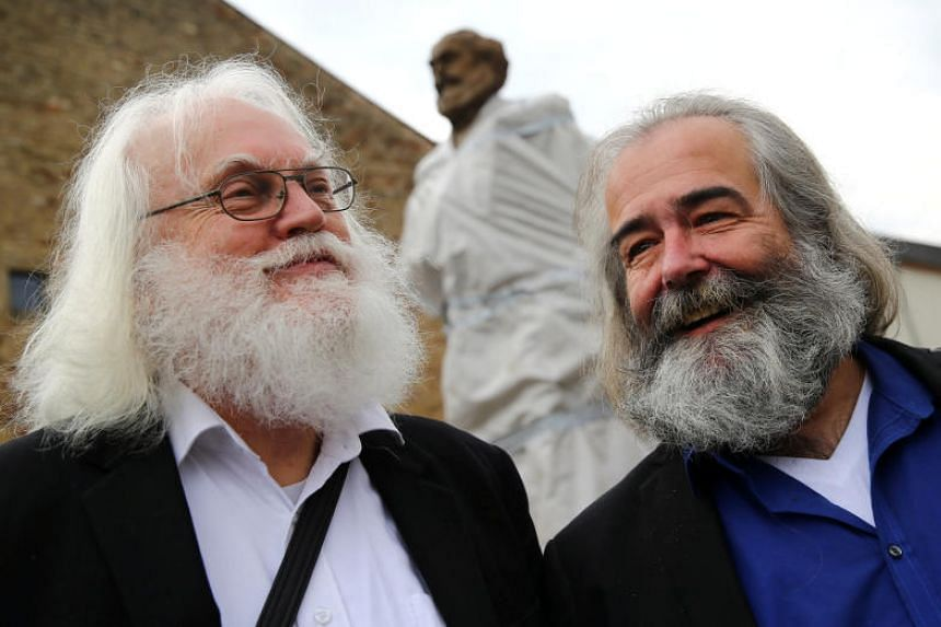Michael Thielen and Henning Laufer, two Karl Marx look-alikes, pose in front of the bronze statue of Marx in Trier, Germany on April 13, 2018.