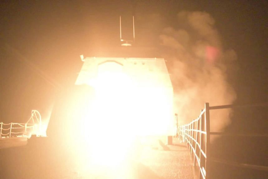 The US Navy-guided missile cruiser USS Monterey is lit as it fires Tomahawk land attack missiles in this still image from Pentagon's video released on April 14, 2018.