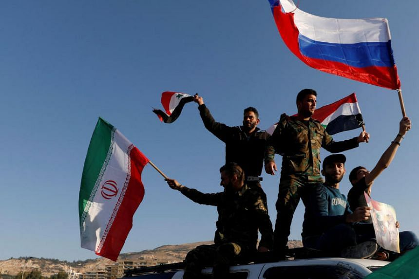 Syrians wave Iranian, Russian and Syrian flags during a protest against US-led air strikes in Damascus, Syria, on April 14, 2018.