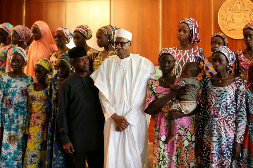 A file photo of President Muhammadu Buhari and Vice President Yemi Osinbajo with some of the 21 Chibok schoolgirls released by Boko Haram, in October 2016.
