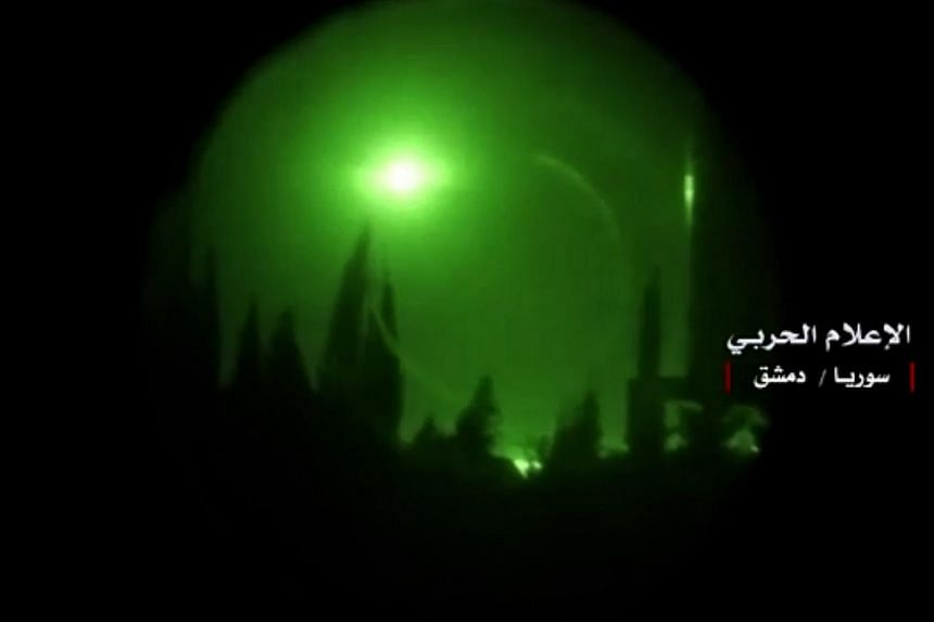 A photo released on April 14, 2018, the twitter page of the Syrian government's central military media shows an explosion in the sky over Damascus seen through a night-vision device after Western strikes reportedly hit Syrian military bases and che
