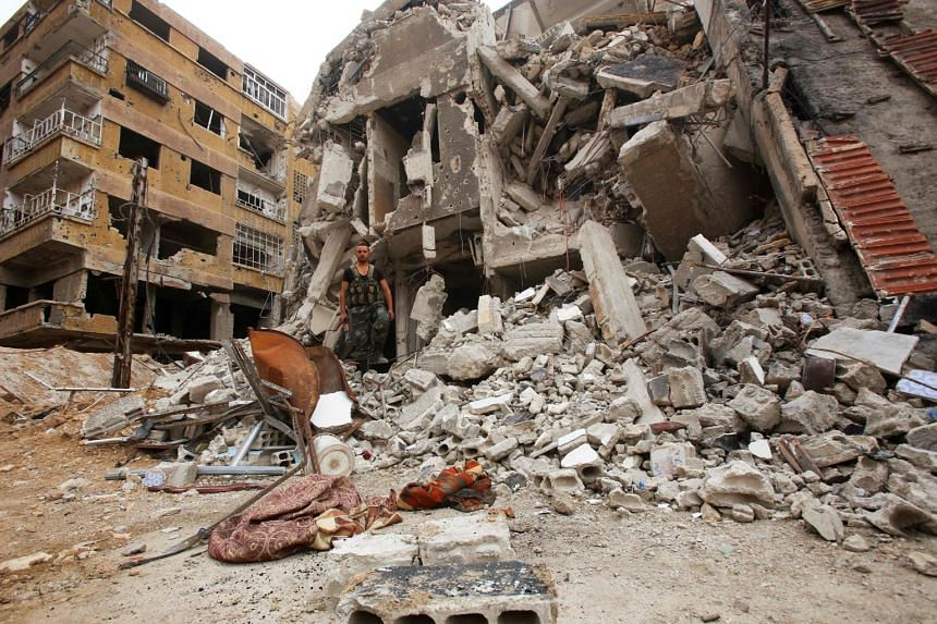 A Syrian government forces soldier walks over the rubble of buildings in the former rebel-held town of Zamalka in Eastern Ghouta, on the outskirts of the capital Damascus, on April 11, 2018.