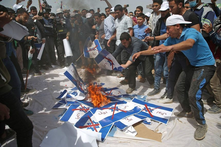 """Palestinians burn Israeli flags with a slogan in Arabic stating """"to its (Israel) demise""""."""