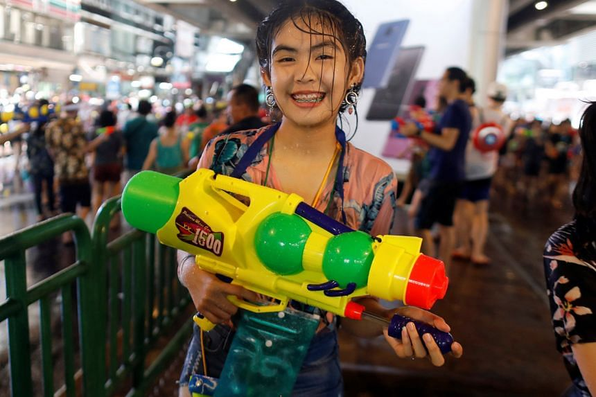 A woman armed with a water pistol at the annual Songkran festival yesterday. Women responded angrily to an official's suggestion that they cover up to avoid being assaulted at the festival.