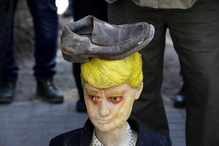 Palestinian protesters hit an effigy of US President Donald Trump with shoes during a demonstration against the military action in Syria in the West Bank City of Nablus.