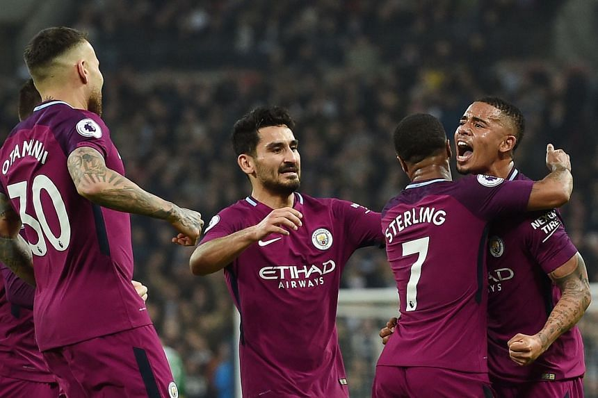 City's Raheem Sterling (second right) celebrates with team mate Jesus (right) after scoring his side's third goal.