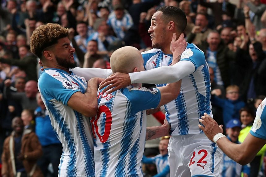 Huddersfield Town's Tom Ince celebrates with Steve Mounie and Aaron Mooy after scoring.