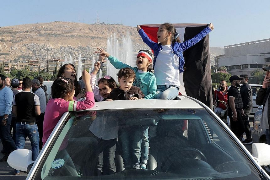 Syrian children, one of them holding a national flag, at a gathering to show support for the Syrian government in Umayyad Square in Damascus yesterday. Unfazed by the missile strikes, crowds of people converged on the famed square to rally behind Syr