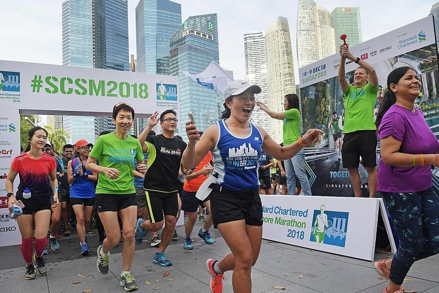 Minister Grace Fu (in green) leading participants on a 4km community run at Marina Bay to kick off this year's Standard Chartered Singapore Marathon. Flagging them off are Judy Hsu, Stanchart's CEO for Singapore and Asean markets, and Geoff Meyer, ma