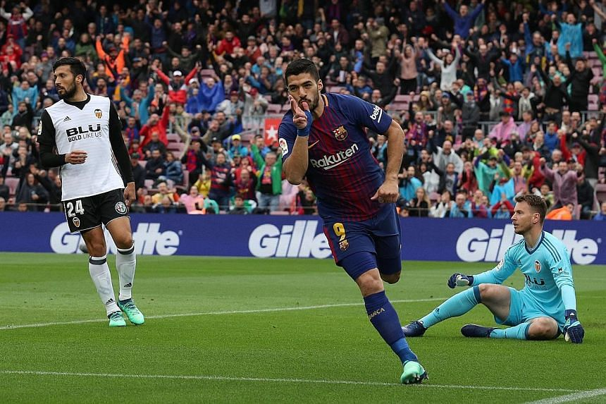Barcelona striker Luis Suarez opening the scoring in the 15th minute against Valencia at the Nou Camp yesterday. The Spanish league leaders are now six games away from becoming the first LaLiga side to complete a 38-game unbeaten season.