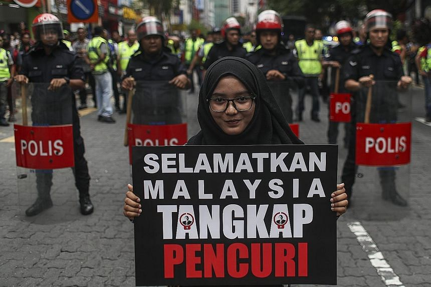 """A protester holding a placard during the #Tangkap-Pencuri (Nab A Thief) rally in Kuala Lumpur, Malaysia, yesterday. The rally is being held to call for the arrest of financier Low Taek Jho - better known as Jho Low - and """"thieves"""" linked to the finan"""