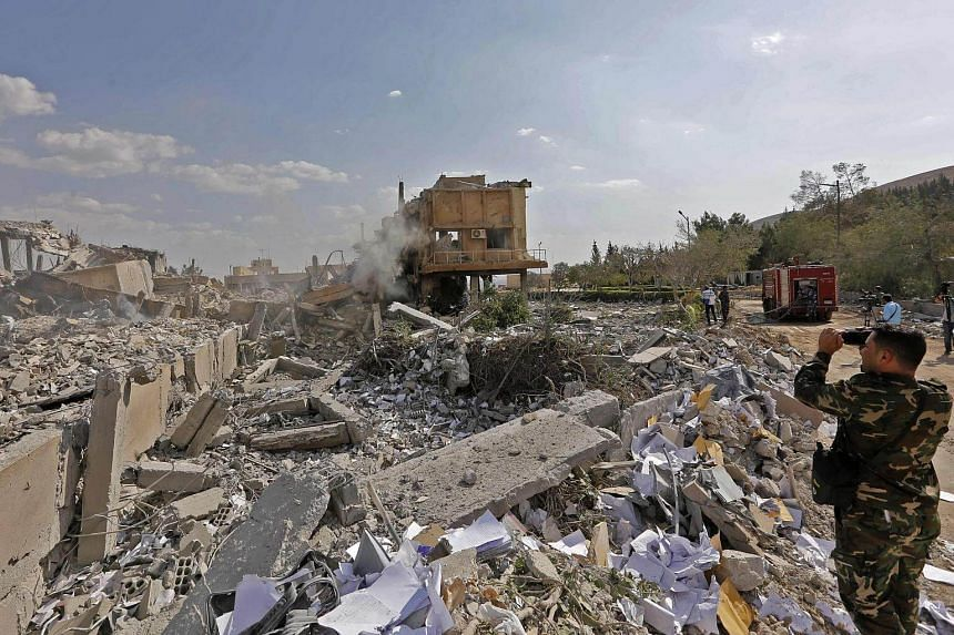 A Syrian soldier takes a picture of the wreckage of a building described as part of the Scientific Studies and Research Centre compound in the Barzeh district, north of Damascus on April 14, 2018.